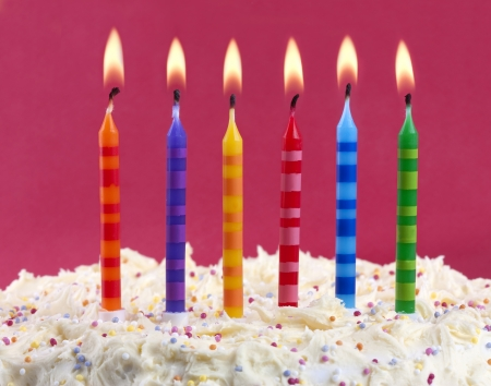 birthday cake with 6 coloured candles on a red background