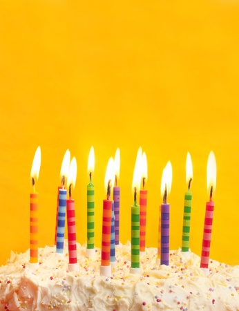 joyeux anniversaire: happy birthday cake shot on a yellow background with candles and lots of space