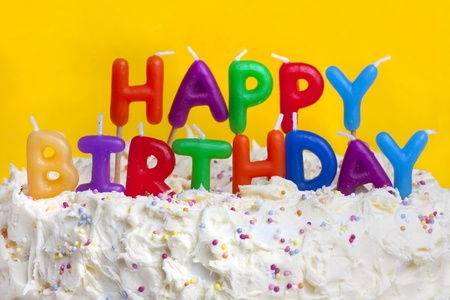 cake with icing: happy birthday cake shot on a yellow background with candles Stock Photo