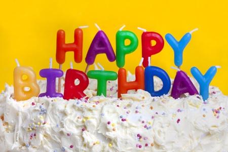 pastel de cumplea�os: Tarta de cumplea�os feliz dispar� sobre un fondo amarillo con velas Foto de archivo