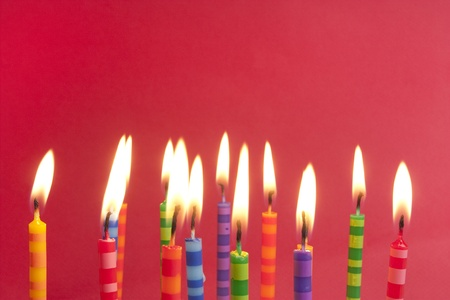 alight: Candles alight on a red background, big group of striped designs