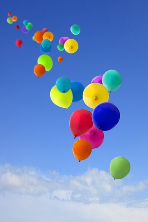 summers day with a host of coloured balloons floating into the blue sky