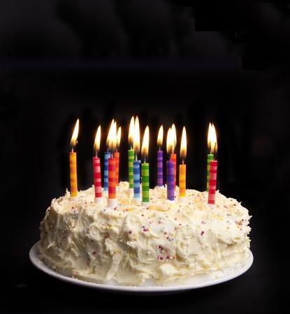 pastel aniversario: pastel sobre un fondo negro con velas prender fuego Foto de archivo