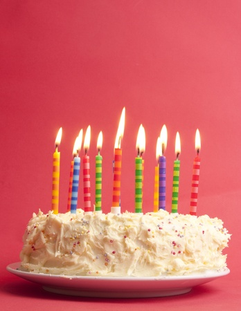 pastel de cumplea�os: pastel de cumplea�os con una gran cantidad de velas rayas lindos dispar� sobre un fondo rojo Foto de archivo