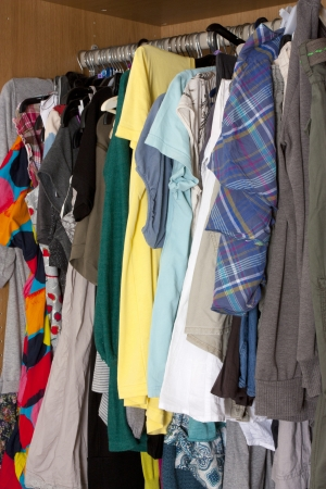 messy clothes: lots of clothes hanging up in a messy way in a womens wardrobe Stock Photo