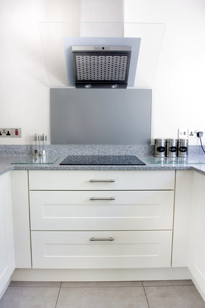 splashback: modern kitchen with white units and extrator fan and hob