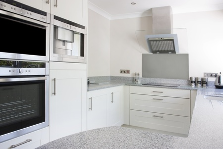 stainless steel kitchen: modern kitchen with built in ovens and hob and extractor fan