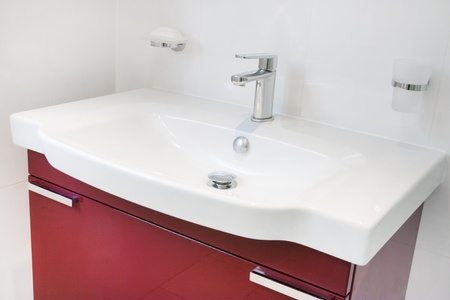 Contemporary modern bathroom red cabinet and built in sink and taps photo