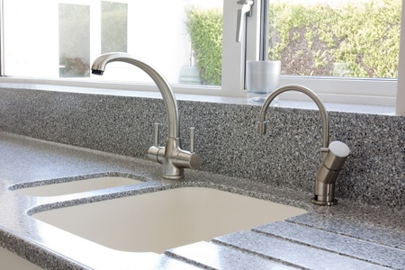 hot water tap: Modern kitchen granite worktop and ceramic sink with mixer tap Stock Photo