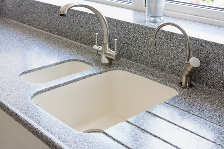 granite kitchen worktop and ceramic sunken sink with hot water tap and normal modern tap Banco de Imagens