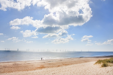 Spring day in caister on sea in the uk with wind turbines out at sea photo