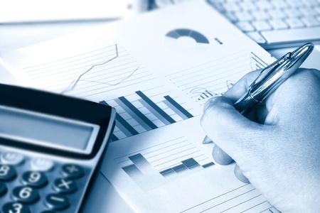 analog�a: calculadora y gr�ficos que representa un rendimiento financiero empresarial Foto de archivo