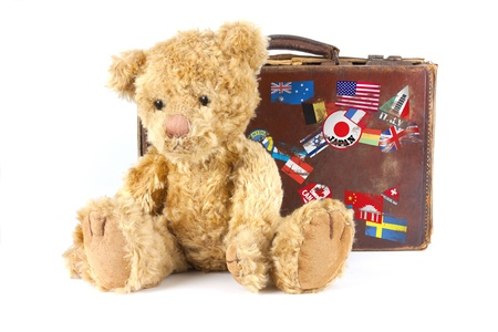 packing suitcase: studio shot of a teddy bear and vintage old suitcase with world stickers isolated on a white background