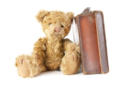 childs teddy bear sitting next to an old vintage suitcase photo