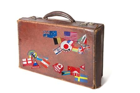 maleta: antigua maleta de estilo vintage con un mont�n de pegatinas y banderas de todo el mundo sobre un fondo blanco
