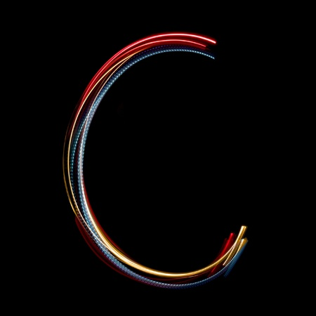 Letter C on a black background made with light painting torches photo