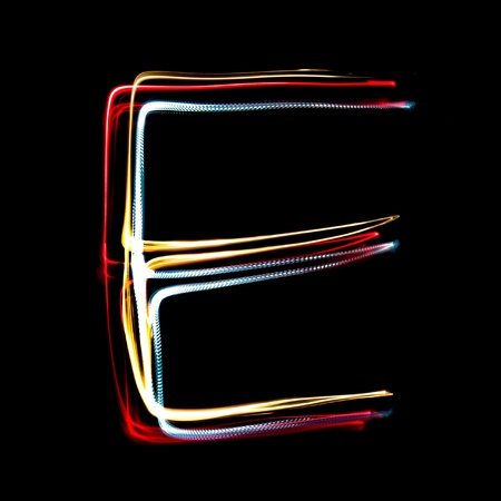 affect: Letter E on a black background made with light painting torches Stock Photo