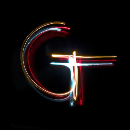 Letter G on a black background made with light painting torches photo