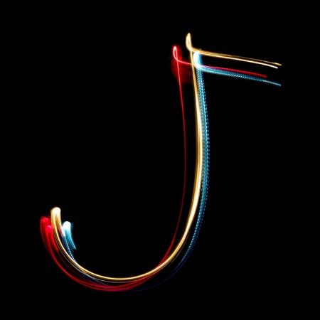 Letter J on a black background made with light painting torches photo