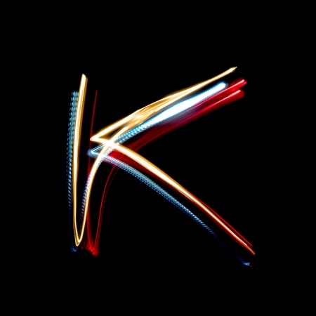 Letter K on a black background made with light painting torches photo