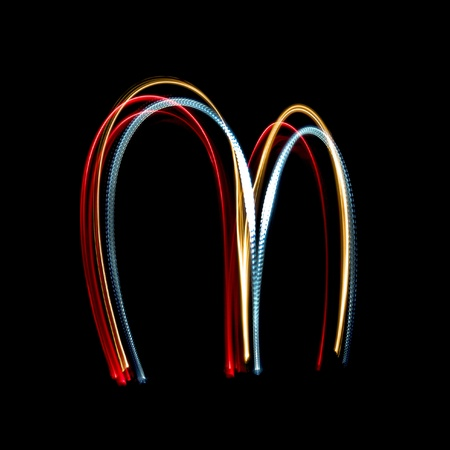 Letter M on a black background made with light painting torches