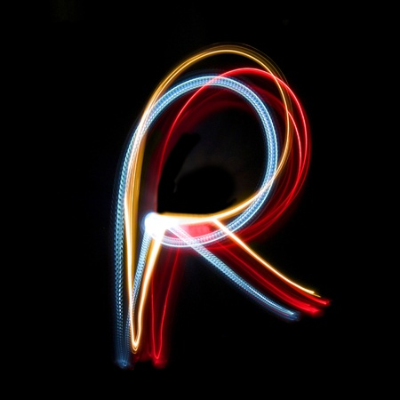 Letter R on a black background made with light painting torches photo