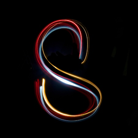 Letter s on a black background made with light painting torches photo
