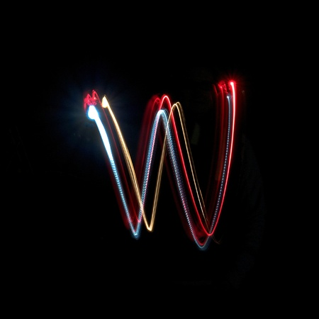 Letter W on a black background made with light painting torches photo
