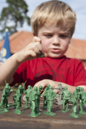 4 year old blonde boy playing toy soldiers photo