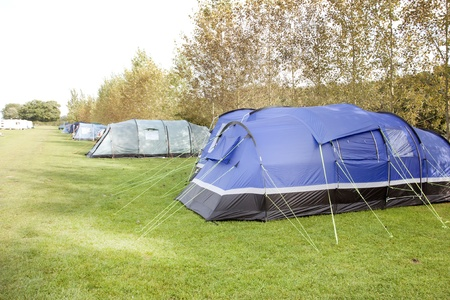 campsite: row of tents camping outside on green grass in the summer