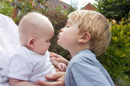 blonde toddler age 4 kissing 6 month old baby, brother and sister Stock Photo - 12173925