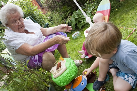 Elderly 70 year old plays with small toddler and baby in summer garden Stock Photo - 12173941
