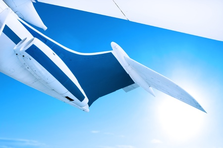 airplane flying against a blue sky, close up of tail fin and engines photo