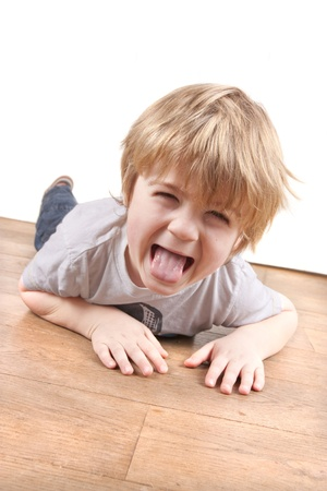 age 5: Boy pulling a funny face playing on the floor Stock Photo