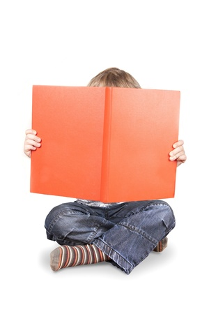 Boy holding up and hif=ding face behind big orange book isolated on a white background photo
