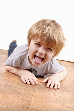 Boy pulling a funny face playing on the floor photo