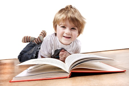 Young child laying on a wooden floor reading a book Stock Photo - 15209703
