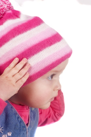 Little girl in pink winter hat isolated on a white background photo