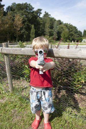 age 5: summer in the woods child playing with a pistol gun