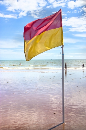 safe water: saety flag on uk beach allowing swimming