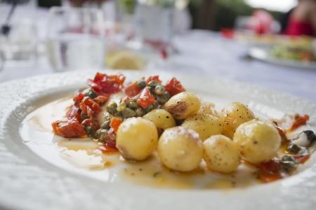 seabass: lubina con la pila de tomates y alcaparras en italiano comedor exterior