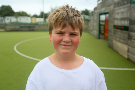 ten year old boy portrait against an all weather sports pitch outside