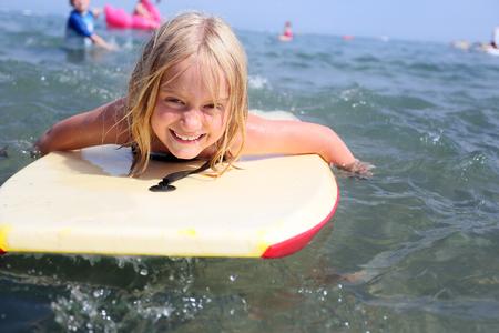 blonde caucasian 7 year old girl bodyboarding in the sea, north wales, uk