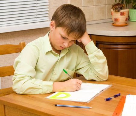 Angry Young boy doing his homework photo