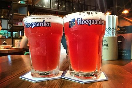 large size: BANGKOK - JUNE 16: Hoegaarden draft Belgium beer in large size glass on counter bar in pub was taken in Bangkok, Thailand, on June 16, 2016.