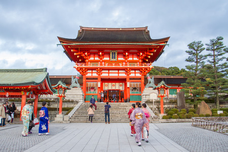 KYOTO - DEC 15 : Traveler walking in the Fushimi Inari Taisha Shrine on 14 Dec 2015. The shrine sits which is 233 meter above sea level, and includes trails up the mountain to many smaller shrines.