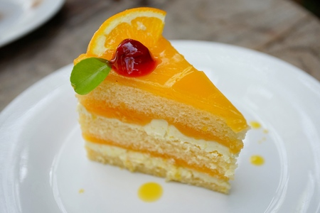 orange cake with orange and cherry topping on the wood table Stock Photo