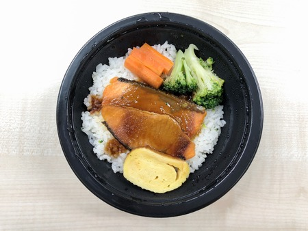Salmon grilled with rice in the food container on the table