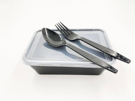 Black Plastic food container with spoon and fork on white background
