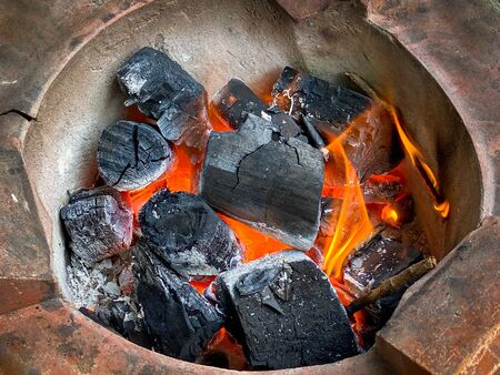 Burning charcoal in stove before cooking food